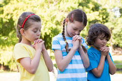 Children saying their prayers in park Stock Photo