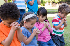 Children saying their prayers in park Stock Photography