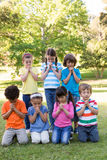 Children saying their prayers in park Royalty Free Stock Images