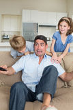 Children scaring father watching television. Mischievous children scaring father watching television on sofa at home Royalty Free Stock Image