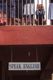 Children at School in Africa. A child looks out through balcony of school in Tanzania with sign below reminding them to speak English Stock Photo