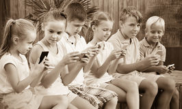 Children in school age looking at mobile phones and sitting outd Stock Photography