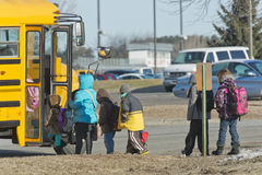 Children at the School bus on a cold morning. A group of children at the school bus on a cold morning in Minnesota Royalty Free Stock Photos