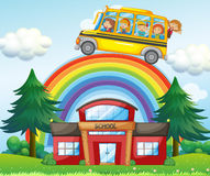 Children on school bus riding over the rainbow Royalty Free Stock Photography