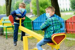 Free Children School In Medical Masks Play At A Quarantine Playground During A Coronavirus Pandemic Stock Photography - 181558512