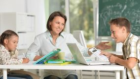 Children at school sit in the classroom with teacher stock photo