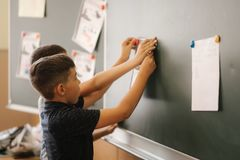 Children in school stand by the blackboard. Elementary school. education.  stock images