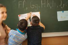 Children in school stand by the blackboard. Elementary school. education.  royalty free stock photos
