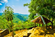 Mountain view of a rest hut with lush green forest and yellow river in East Asia stock photography