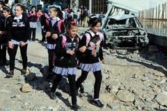 Children after school walk through debris after Israel bombings in Palestine.  Stock Photo