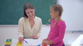 Children schooling, smiling woman educator checks homework at little learner girl at table near blackboard in classroom. Of elementary school stock video footage