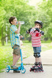 Children with scooter and rollers drink water Royalty Free Stock Photography
