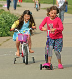 Children on scooters. Photo of a young girls on their bikes and scooters on the coast of whitstable in kent Stock Images