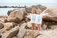 Children on the sea beach. Twins standing against stones and sea water. Royalty Free Stock Images
