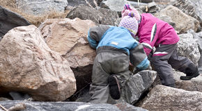 Children searching. For treasures between large rocks Royalty Free Stock Photos