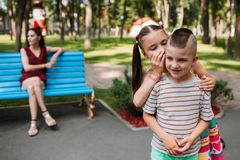 Children secrets behind mother back at park stock images