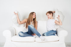 Children sedyat on the couch and pillows fighting. Boy and girl fighting pillows Stock Photos