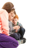 Children sending sms on mobile phone. Three children sending sms on mobile phone. On white Royalty Free Stock Image