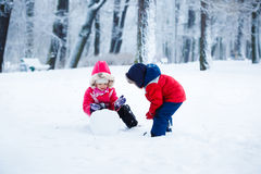 Children shape the snowman. Boy and girl have fun stock photography