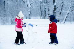 Children shape the snowman. Girl and boy have fun stock photo