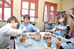 Children shaping clay in pottery studio Stock Photo