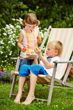 Children sharing fresh fruits in a garden Royalty Free Stock Photo