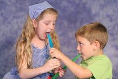 Children sharing popsicles. Shot of children sharing popsicles Stock Photo