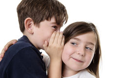 Children sharing a secret. Two children whispering into each others ear sharing a secret stock photography