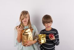 Children shocked by bad gifts. Children shocked by bad the gifts Royalty Free Stock Images