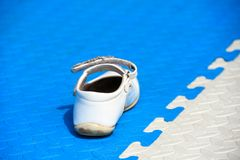 Children shoes are on the playing mat royalty free stock images