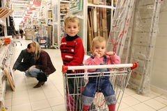 Children in shopingcart and couple Royalty Free Stock Photos