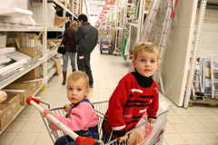 Children in shopingcart and couple. Behind Stock Photo