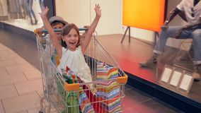 Children shopping day, positive emotional kids having fun in customers trolleys in mall and go past shop windows of stock video footage
