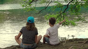 Children on the Shore of Lake. Slow Motion. Summer. Unrecognizable boy and girl sitting on the shore of the peaceful lake. Slow motion stock footage