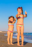 Children show thumbs up on the beach. Stock Photos