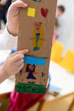 Children is showing drawing made on cardboard. Cardboard royalty free stock photo