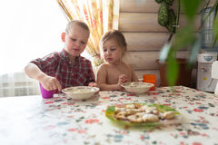 Children are siblings having breakfast, milk, cookies, lifestyle. In the village, children brother and sister, cottage cheese for breakfast in the village at Royalty Free Stock Image