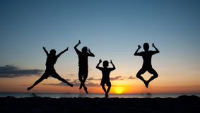 Children in Silhouette against the Sunset. Children jumping with joy as the sun sets behind them Stock Photos