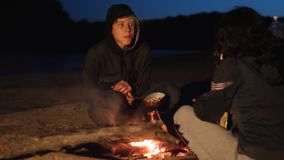 Children silhouette kids teen sit by the fire eating popcorn at night campfire. travel hiking adventure camping. Children silhouette kids teen sit by fire eating stock video