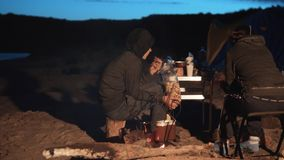 Children silhouette kids teen sit by the fire eating popcorn at night campfire. travel hiking adventure camping. Children silhouette kids teen sit by fire eating stock footage