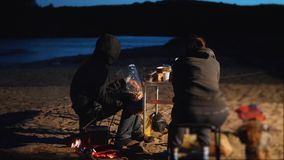Children silhouette kids teen sit by the fire eating popcorn at night campfire. travel hiking adventure camping. Children silhouette kids teen sit by fire eating stock video footage