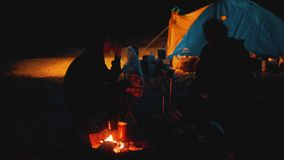 Children silhouette kids teen sit by the fire at night campfire. travel hiking adventure camping adventure camping. Children silhouette kids teen sit by fire at stock video footage