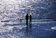 Children Silhouetted on the Water. Two children are standing in the water at a beach silhouetted against the sunlight. Horizontal shot Royalty Free Stock Photo