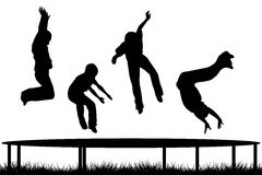 Children silhouettes jumping on garden trampoline Royalty Free Stock Photography