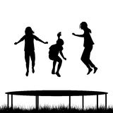 Children silhouettes jumping on garden trampoline Royalty Free Stock Photo