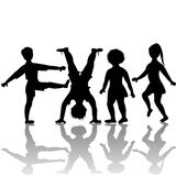 Children silhouettes playing Royalty Free Stock Image
