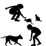 Children silhouettes playing with pets Stock Photos