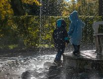 Children silhouettes under the rain of the fountain. Drops and splashes of water illuminated by sunlight royalty free stock photos