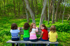 Children sister and friend girls sitting on forest park bench. Children sister and friend girls sitting on park bench looking at forest and smiling Royalty Free Stock Photography