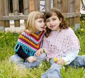 Children sister girls whisper in ear meadow spring. Fence yellow flowers Royalty Free Stock Photos